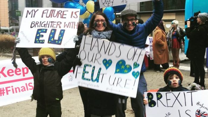 "A family of Brexit protestors with placards including ""My future is brighter with EU"" and ""Hands off our f-EU-ture""."