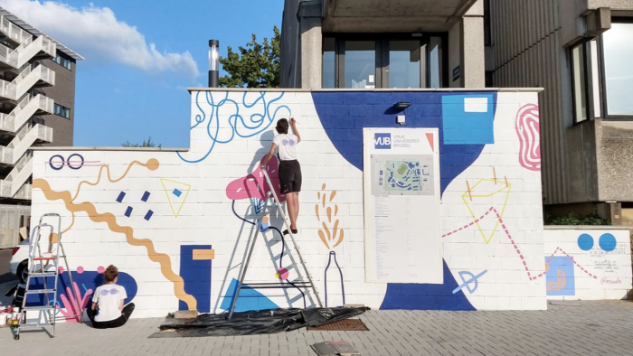 Two people painting a mural on an external wall